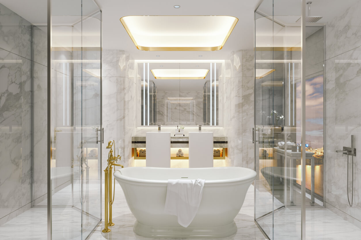 A glam white bathroom done with white luxurious marble tiles and golden details.
