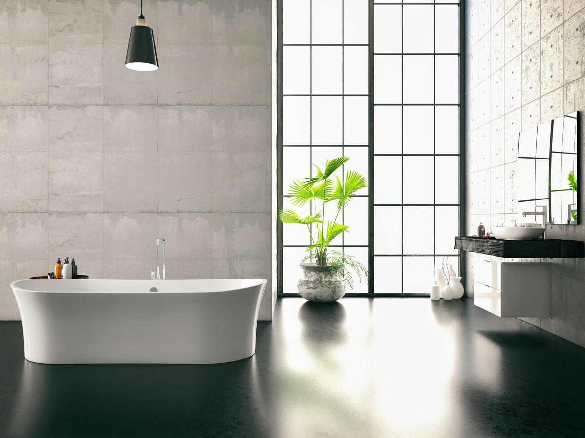 White bathtub in spacious bathroom with a black floor.