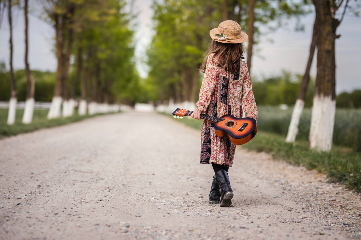 Child walking down the road with ukulele guitar in her hand