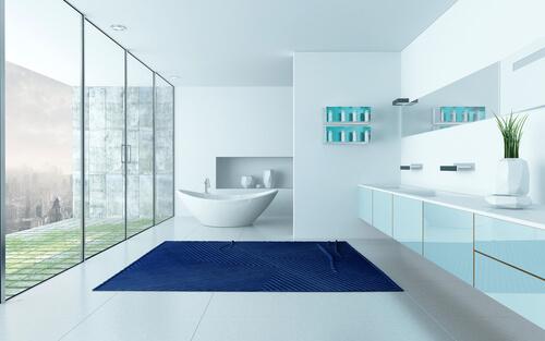 white bathroom with large blue bath rug on white floor.