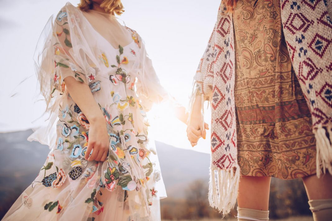 Two hippie women holding each other hands in nature.
