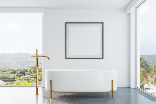 bath with gold fittings in front of a window
