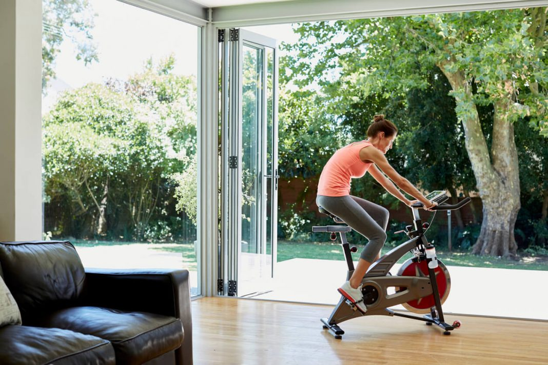 ull length of woman working out on exercise bike at home