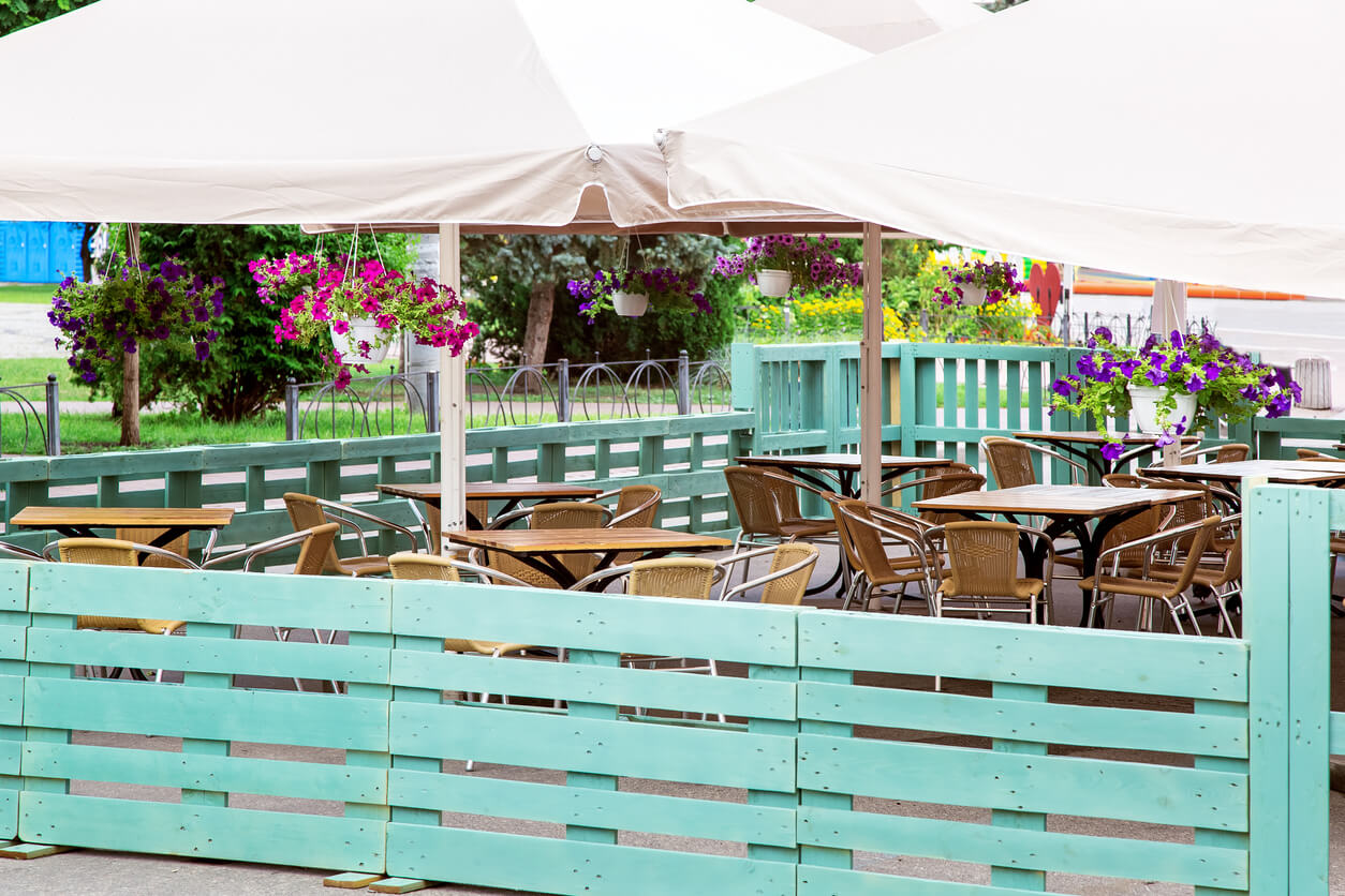 a free wooden table with a wicker chair of an outdoor cafe under an umbrella with hanging flowerpots and blooming petunias fenced with a wooden fence of green painted pallets.
