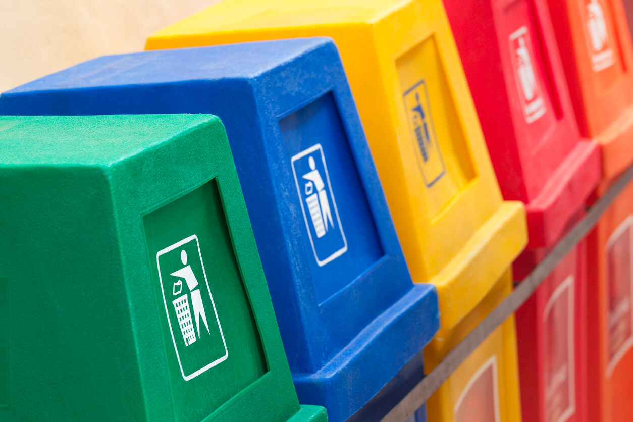 A row of recycling bins in different colors at a recycling station