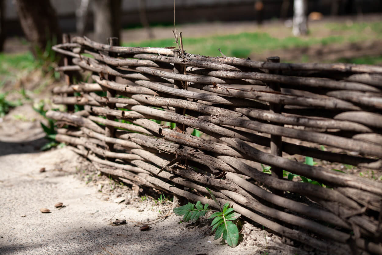 A woven wooden fence made of thin old branches in the countryside. Village yard fence. Shallow depth of field.