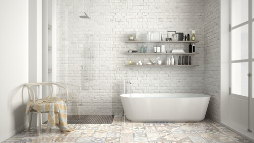White brick wall and patterned floor tiles in a neutral bathroom