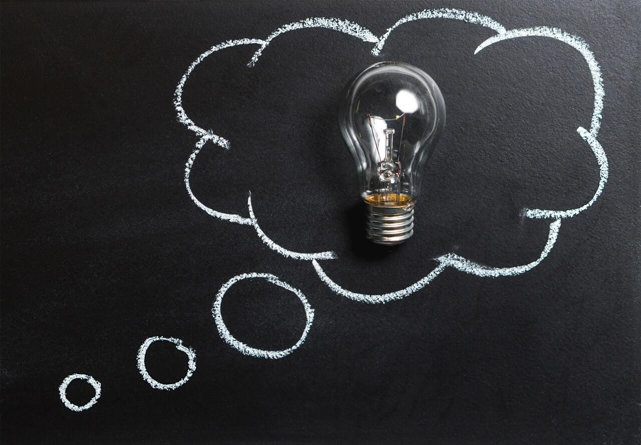 Lightbulb in a cloud drawn on a board