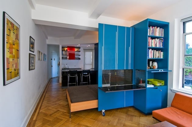 blue room divider with bed behind it.