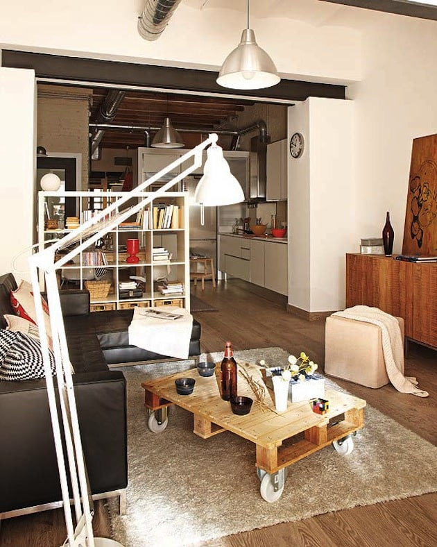 Bookcase divider in small studio with large floorlamp in forefront.