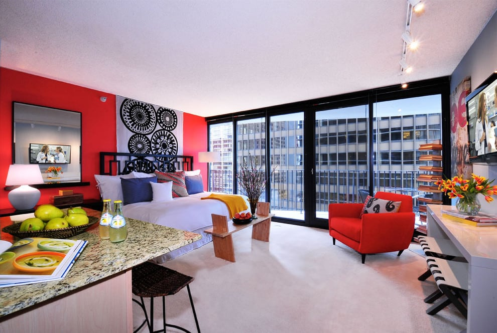 Panoramic window with red accents in small studio apartment.