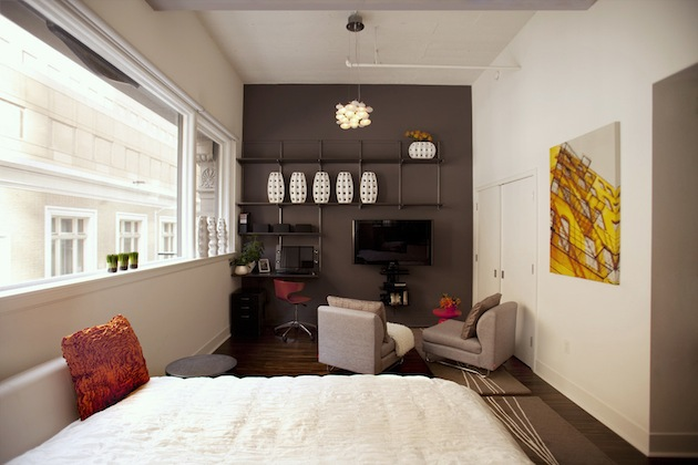 studio appartment with dark grey back wall and bed in forefront.