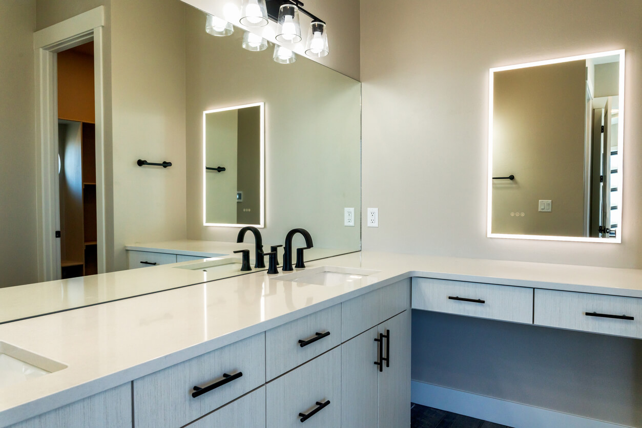 Contemporary Style Well Lit Bathroom With Sinks, Cabinets, And Lighted Vanity Mirror