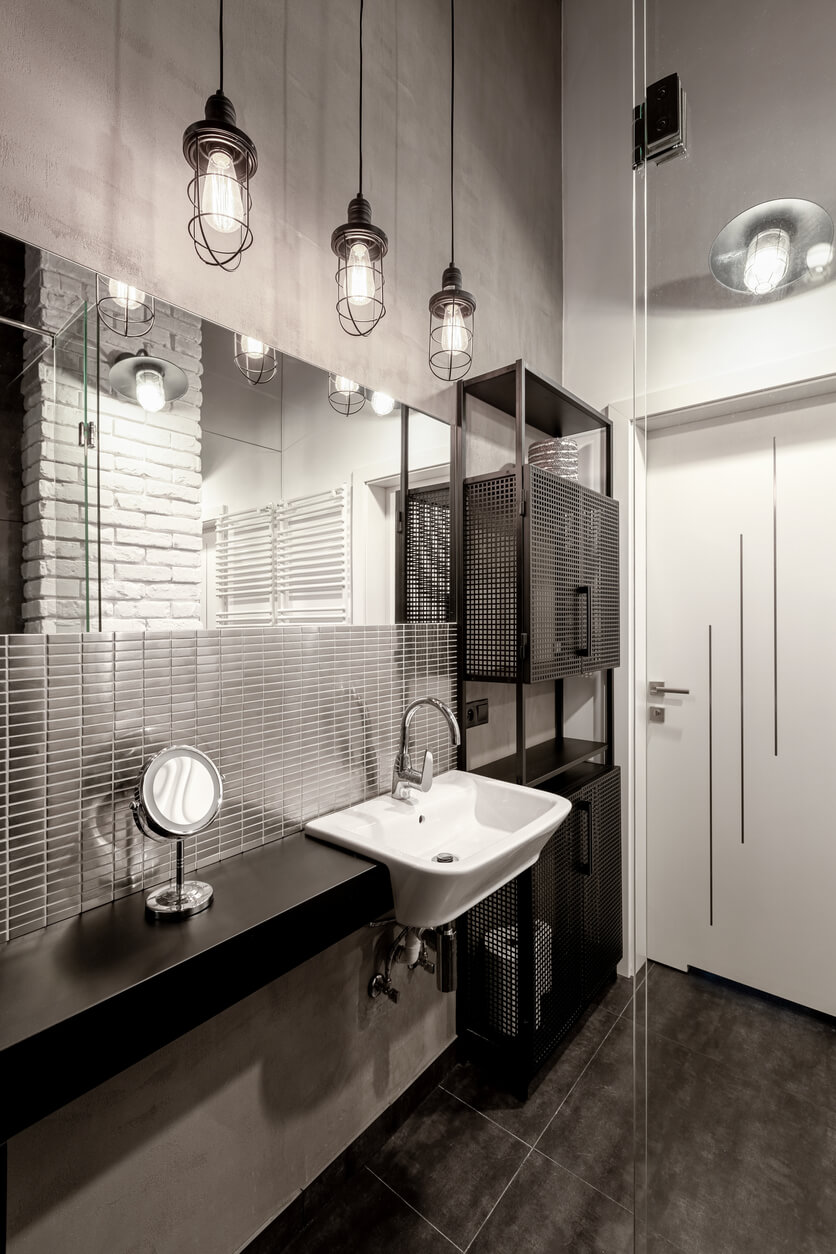Dark and stylish bathroom in gray and black with industrial style lamps.