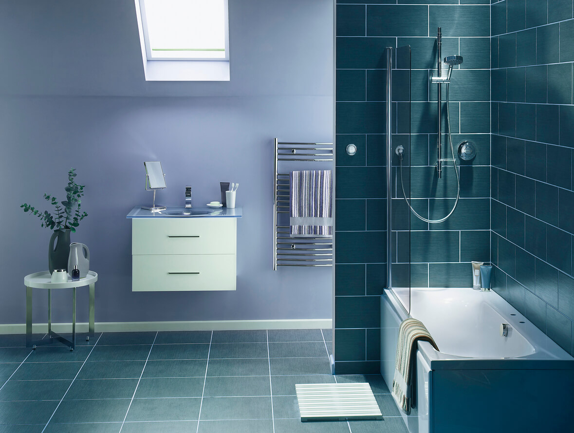 The interior of a simple, modern bathroom in a , cool, blue-gray tone. There is a sink, mirror,bath and shower, a hand towel holder. There are dark rectangular tiles on the wall, and lighter gray tiles on the floor.