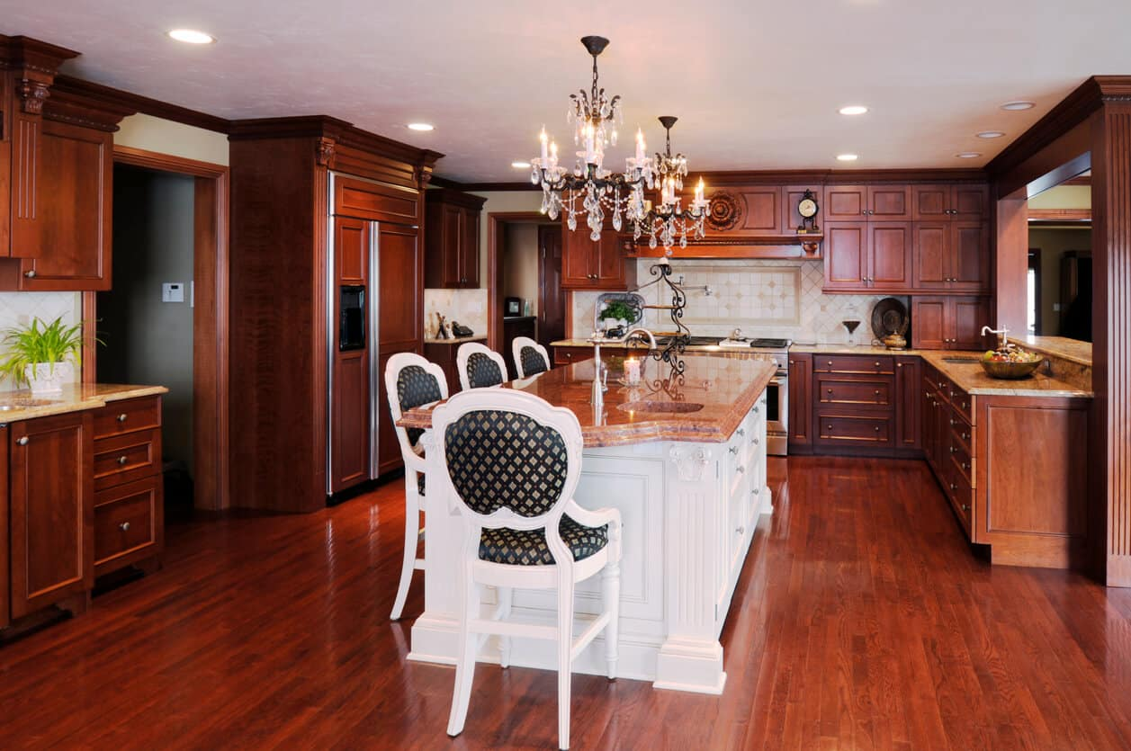 This amazing kitchen features granite counter tops, stunning woodwork including hardwood cabinets and floor, and custom lighting.