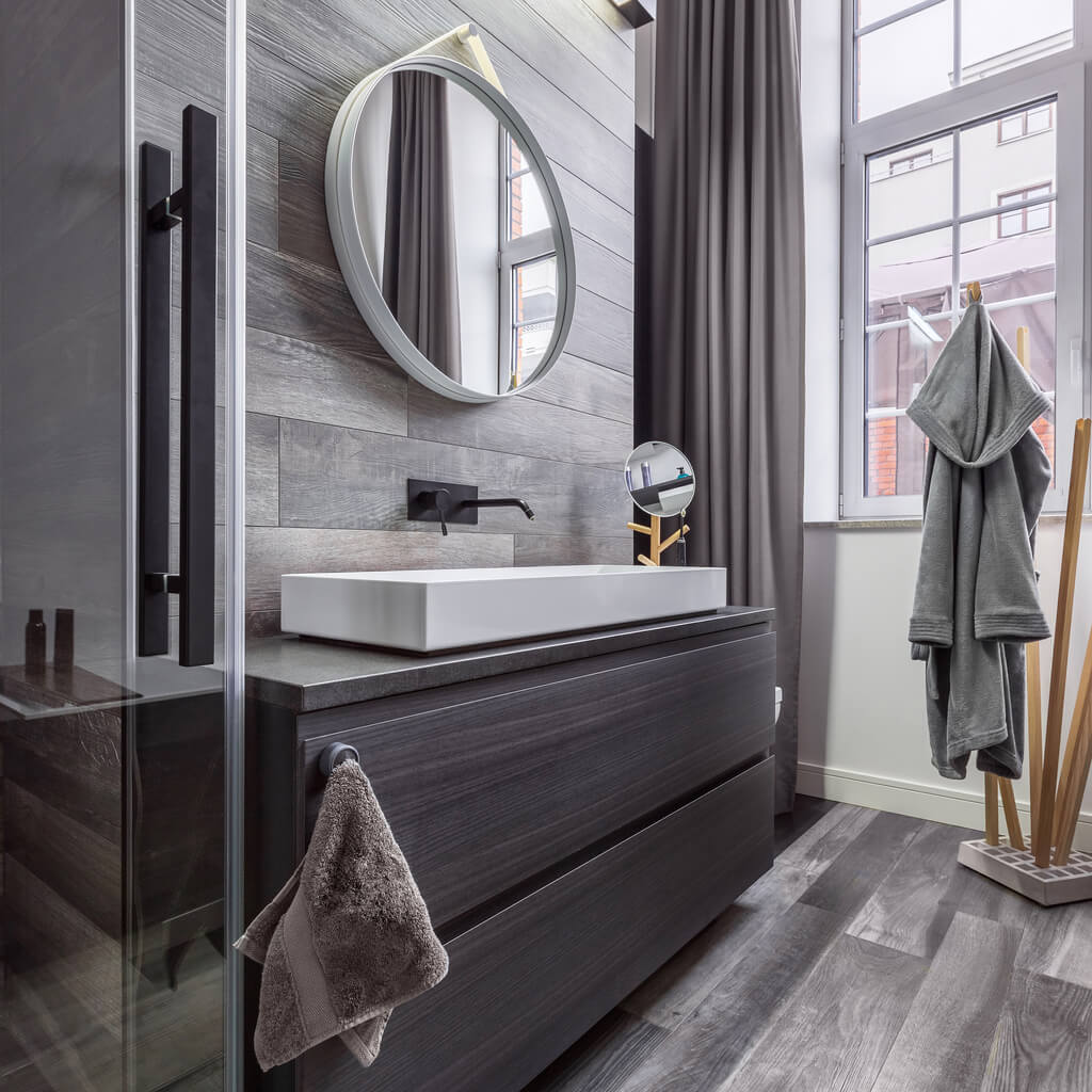Stylish grey wooden bathroom with round mirror and countertop basin