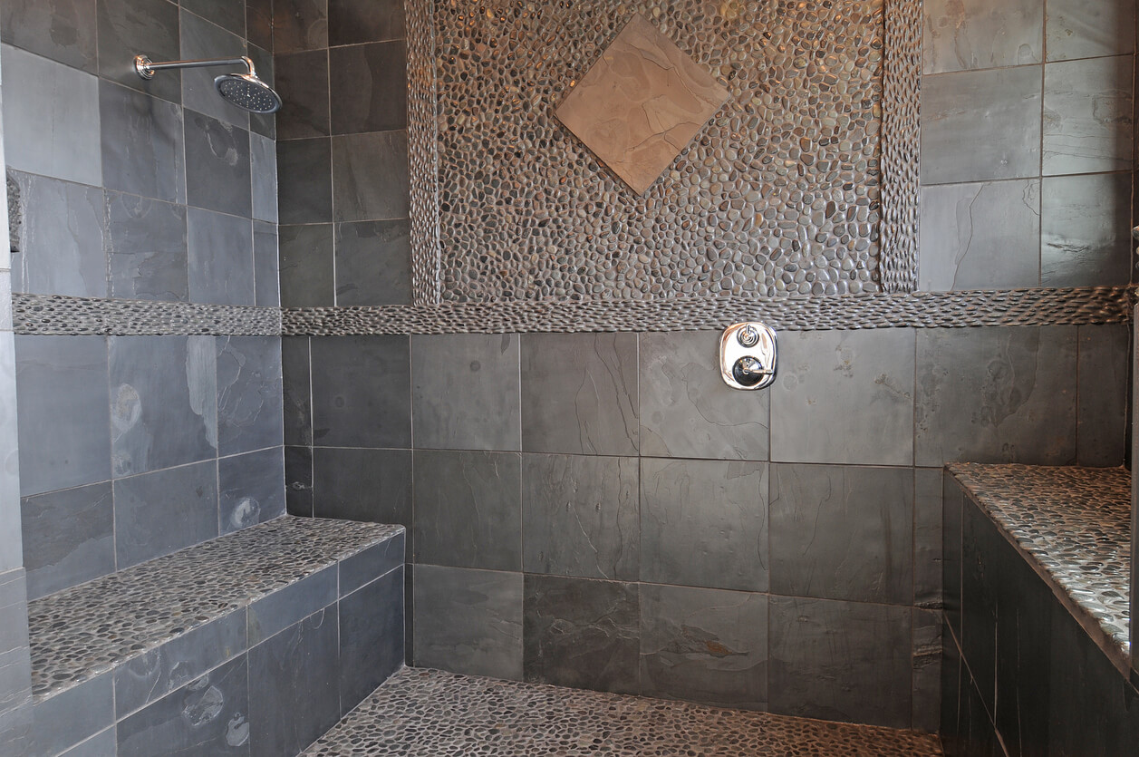 Large shower room with dark natural stone tiles