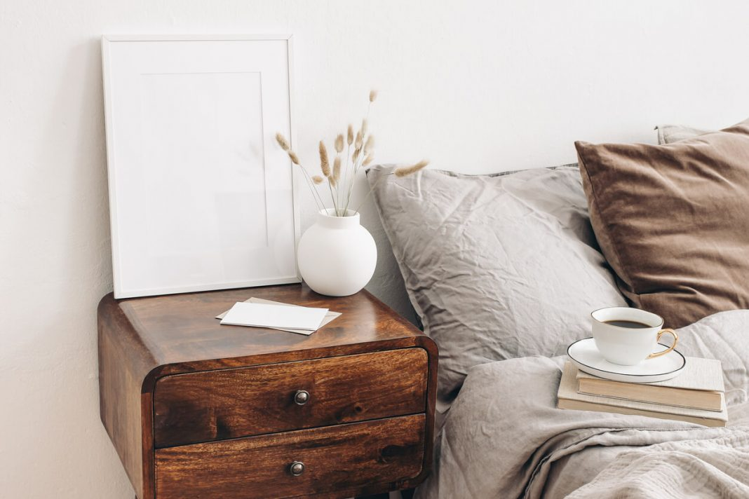 Portrait white frame mockup on retro wooden bedside table. Modern white ceramic vase, dry Lagurus ovatus grass. Cup of coffee and books in bed, beige linen pillows in bedroom. Scandinavian interior.