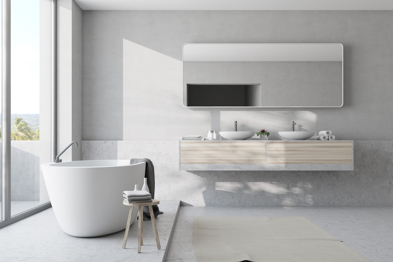 White bathroom interior with a concrete floor, a panoramic window and a white tub with a towel on it. A double sink.