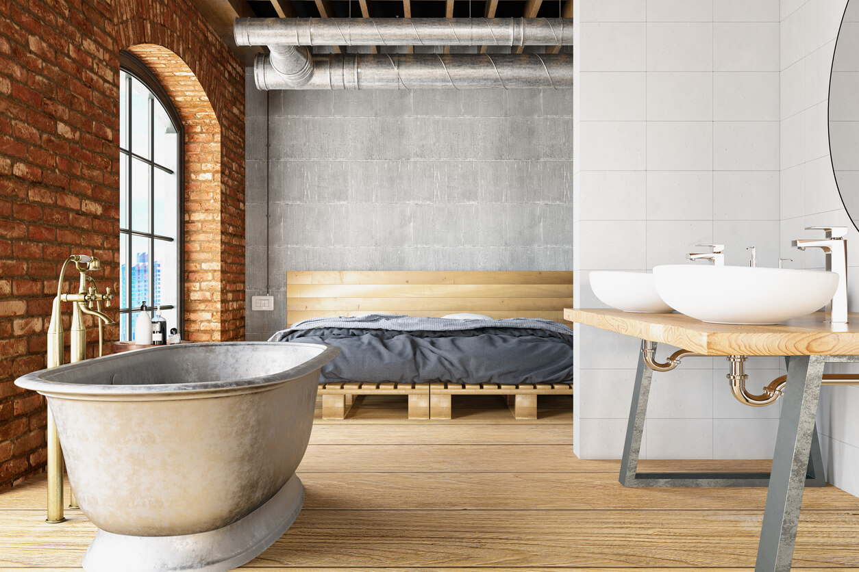 Open plan bathroom with metal freestanding bath and industrial sink shelf.