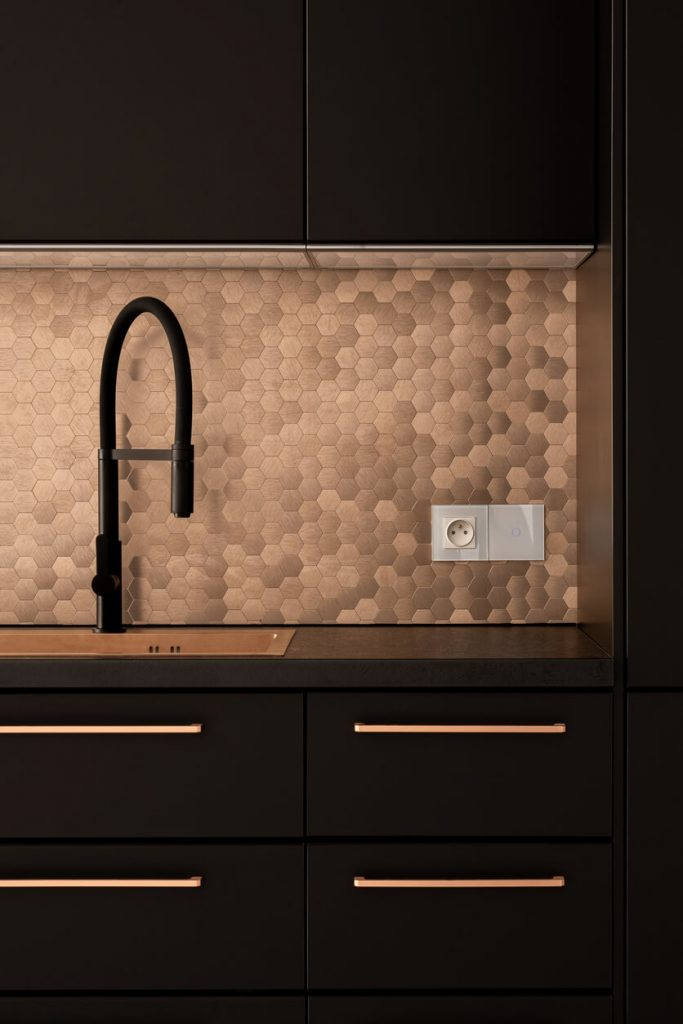 Black kitchen furniture with golden handles, sink, hexagonal wall tiles and black faucet