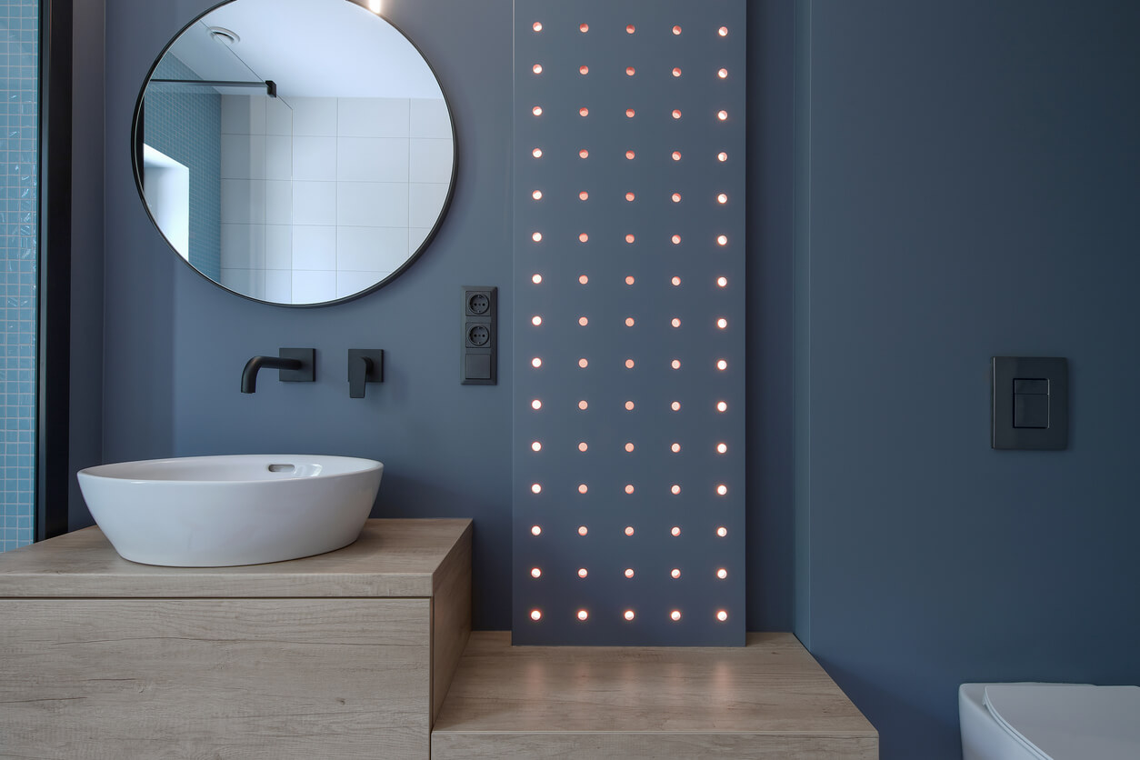 nterior photography of modern minimalist bathroom with navy blue walls and wood furniture