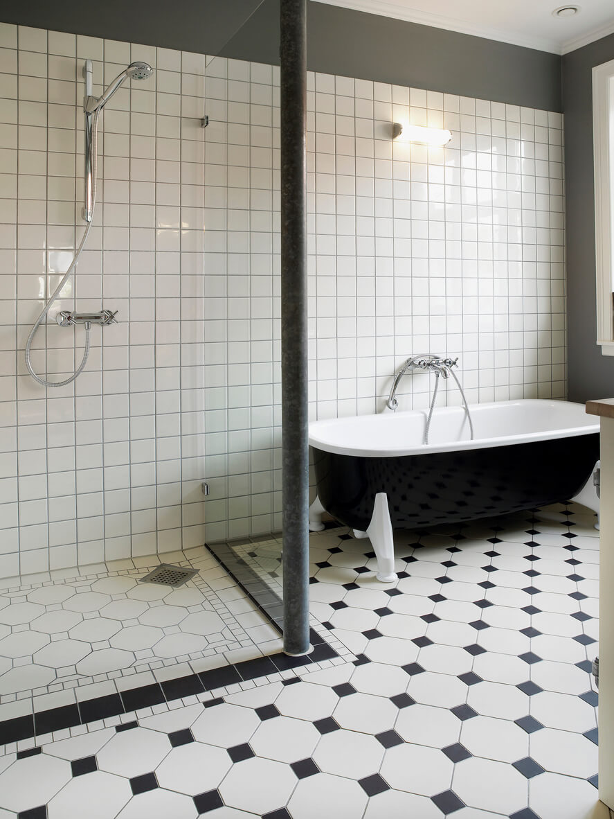 Black and white floor tile with walk in shower and black roll top bath.