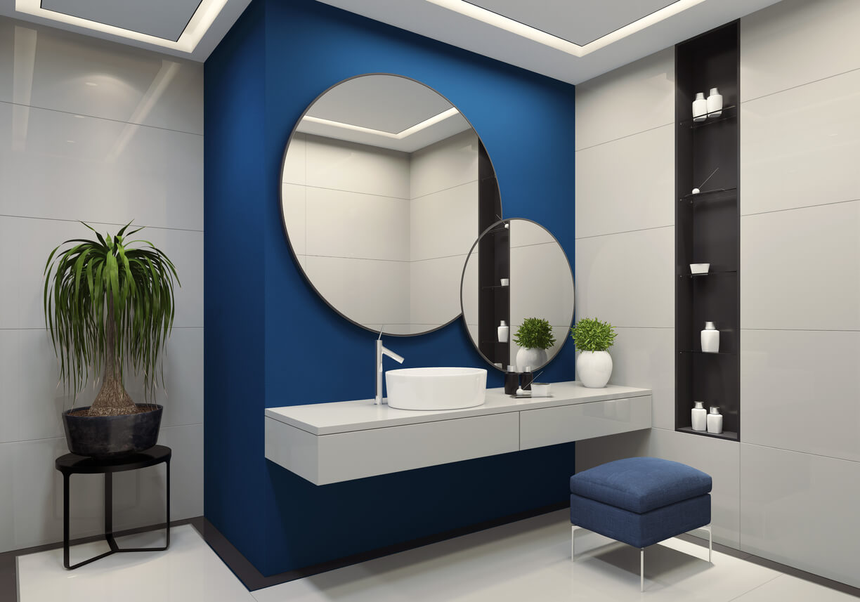 ontemporary minimalist blue and white bathroom two round mirrors with black frames are on the royal blue wall. round ceramic washbasin and stainless steel basin tap is on top of the white vanity unit with two drawers. blue vanity stool is under vanity unit. walk-in shower with large white tiles and staineless steel shower panel with glass door. black wall shelves with small white cosmetic bottles. ceiling with strip cove lighting with embedded spotlights.