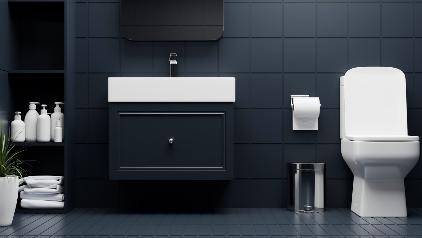 Modern luxury bathroom interior with toilet bowl, stylish cabinet and basin, bathing shelves in dark blue tiles floor and wall.
