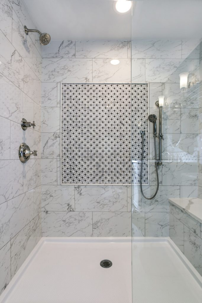 Lovely walk-in shower with carrera Marble Surround and mosaic accent tiles.