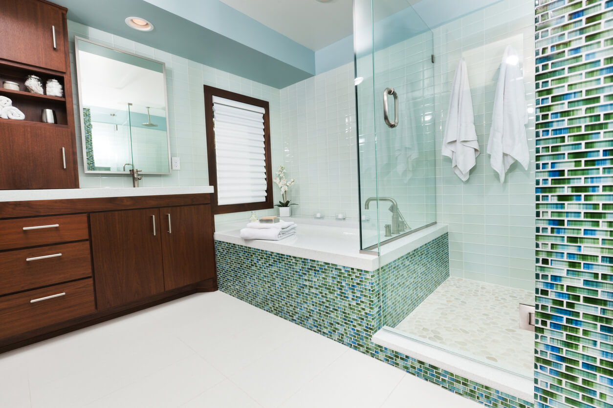 Contemporary residential home bathroom modern design featuring glass shower stall, bathtub, vanity sink and fixtures, and glass wall tiles