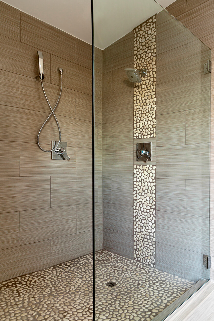 Contemporary shower showing dual shower heads and detail stone work. Also has glass enclosure.