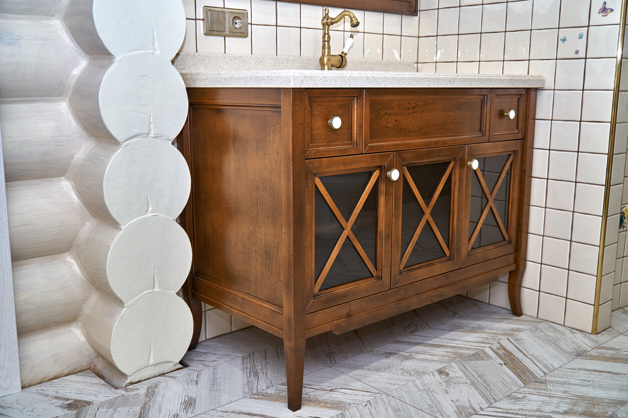 Elegant bathroom vanity cabinet with acrylic countertop located near tiled wall inside luxury water closet. Country style.