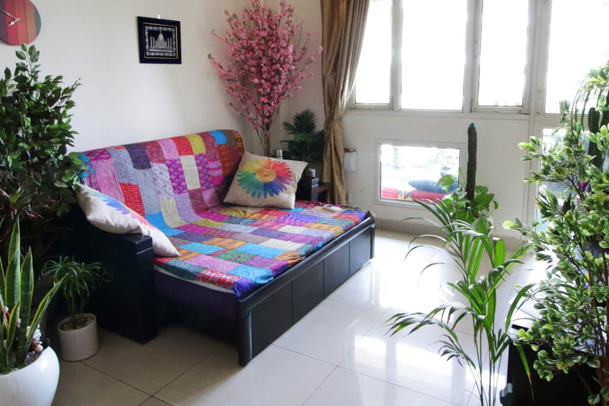 Lounge sofa covered with a brightly, multicoloured patchwork quilt and patterned scatter cushions. The lounge has a white tiled floor and contains plant pots full of a variety of plants.