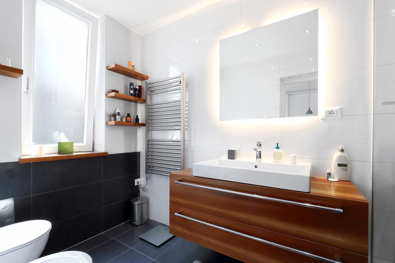 Grey tiles in bathroom with wood floating shelf vanity under wall mirror.