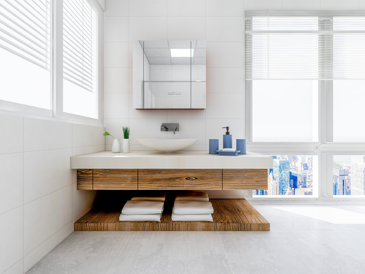 Bathroom, the white cabinet with white clean towels, green plants on the counter, and glass windows next to it