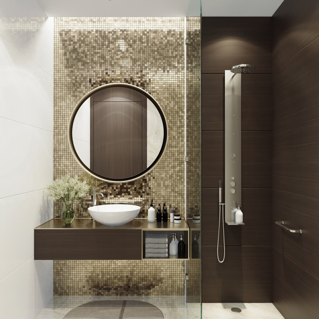 Luxurious bathroom with natural stone tiles and gold mosaic tiles. Round mirror. Small bathroom.