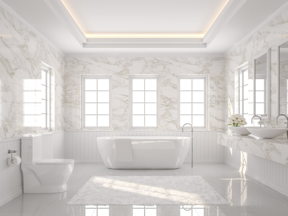 Luxury white bathroom. There are white tile floor and marble wall. The room has more windows. Sunlight shining into the room