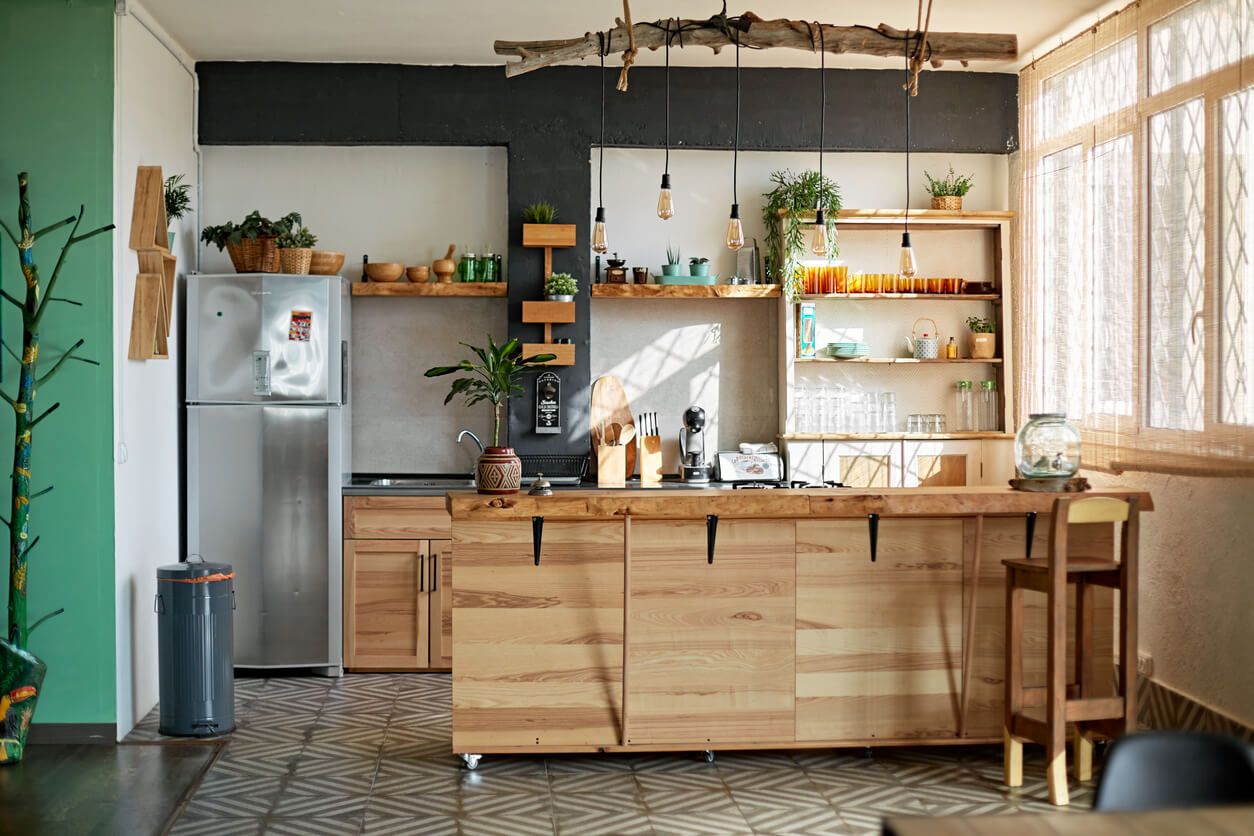 Wide angle view of unoccupied modern kitchen with rustic style including wooden kitchen island and hanging pendant lighting.