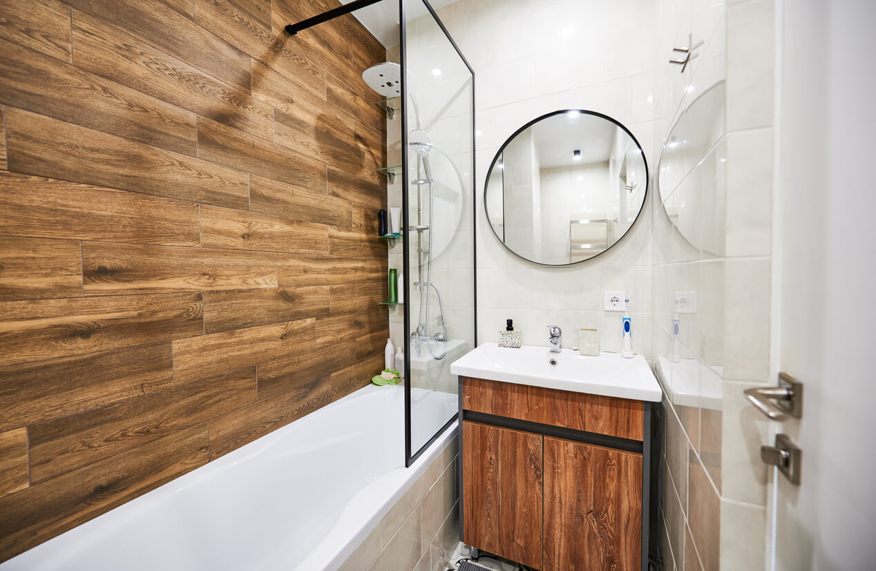 Stylish and comfortable version of bathroom design in small space. White color of rectangular bathtub and wash basin in harmonious combination with round mirror supplemented by wooden decor.