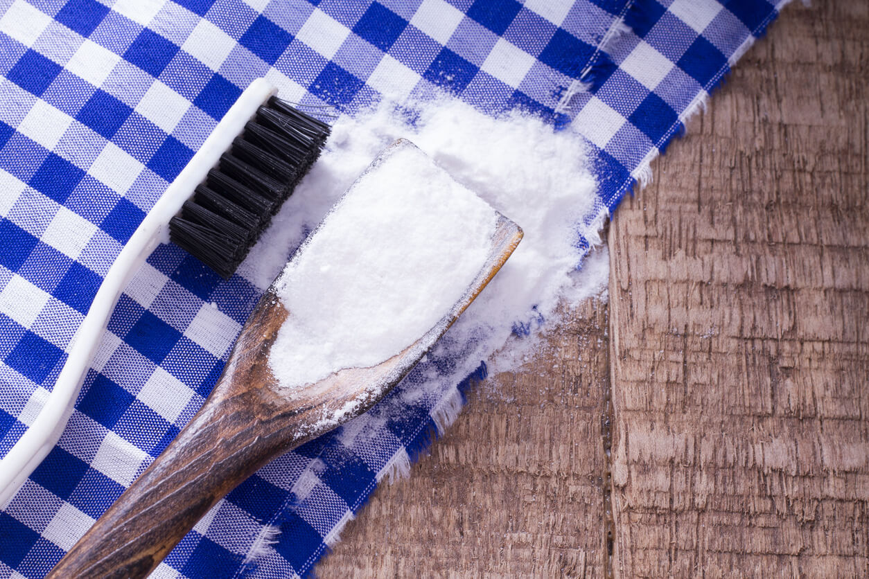 Baking soda and brush on wooden table.