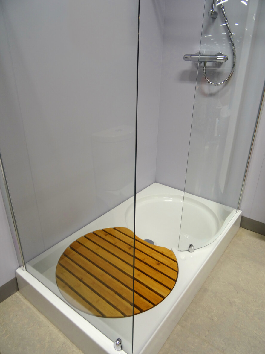 Photo showing a modern bathroom fitted with a large rectangular shower enclosure and shower tray, complete with a slatted wooden teak bath mat, also known as a 'duck board'.